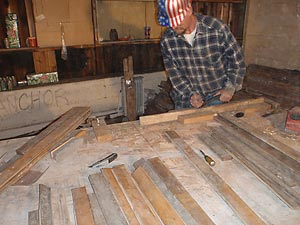 Preparing individual slats of the salvaged maple flooring